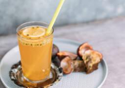 Eistee auf Roibusch Maracuja Basis in einem Glas mit Strohhalm.