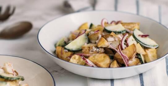 Kreative Rezepte mit Kartoffeln als Hauptzutat. Wie zum Beispiel ein gebackener Kartoffelsalat mit Zwiebeln, Gurken und Joghurtdressing. Hier in einer Schüssel, von der Seite fotografiert.