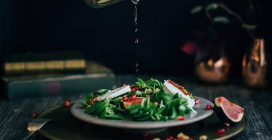 Salatdressing tropft auf einen würzigen Herbstsalat