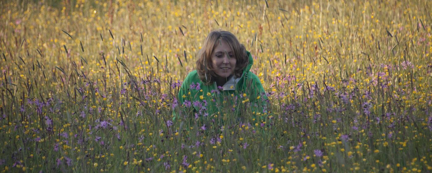 Allgäuer Wildkräuterführerin Ina Tenhündfeld kniet in einer üppigen Wiese