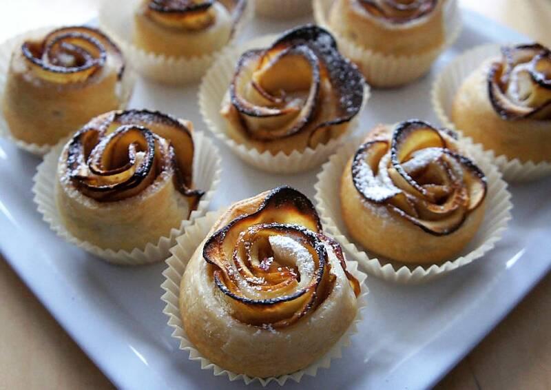 Apfelrosen in Muffin-Förmchen auf einem Teller, knusprig gebacken. Von oben fotografiert.