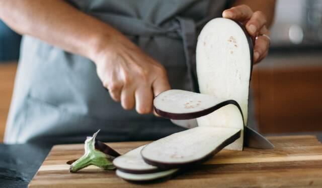 Darf man Auberginen roh essen? Diese Frage beantwortet dir unser Redakteur Florian in diesem Artikel. Auf dem Bild ist eine Aubergine zu sehen, die gerade auf einem Holzbrett in Scheiben geschnitten wird.