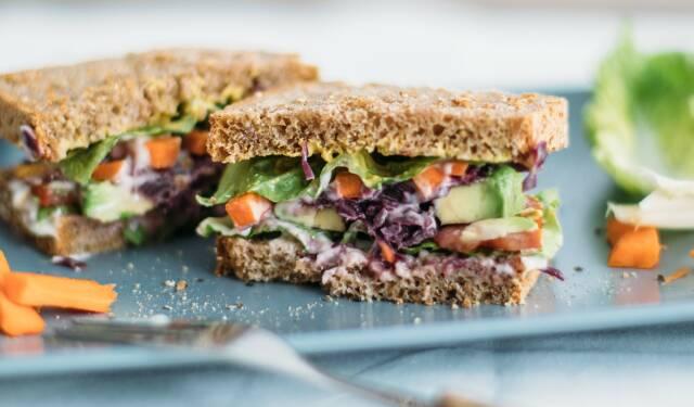 Diese Woche stellen wir dir 5 Gerichte vor, die du super mitnehmen kannst. Wie dieses Sandwich mit Avocado, Tomaten, Gurken und Salat, auf blauem Teller. Von vorne fotografiert.