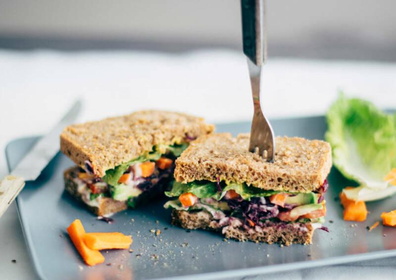 Buntes Sandwich mit sommerlicher Note auf einer grauen Platte angerichtet und von vorne fotografiert.