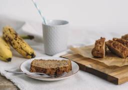 Bananenbrot auf Teller mit Bananen und einer Tasse Milch