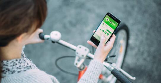 App Vanilla Bean in der Hand einer Frau auf dem Fahrrad