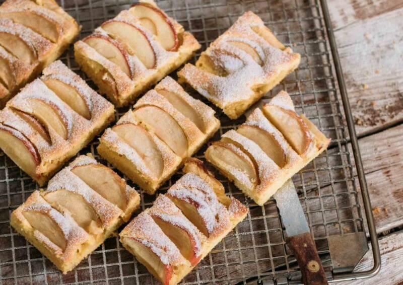 Apfelkuchen vom Blech in Stücke geschnitten, mit Puderzucker darauf. Auf einem Gitter drapiert und von oben fotografiert.