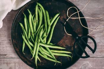Grüne Bohnen von oben auf einem schwarzen Teller