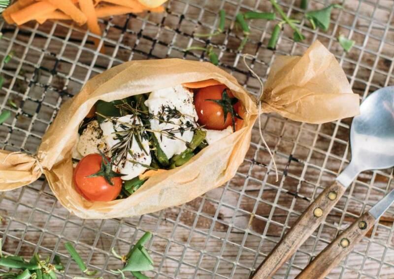 Backpapier-Päckchen mit Gemüse gefüllt auf einem Gitter, von oben fotografiert.