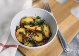 Bratkartoffeln mit Räuchertofu und Zwiebeln und Frühlingszwiebeln in weißer Schüssel auf Holzbrett