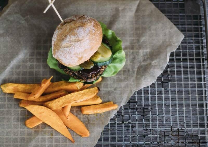 Veganer Burger mit selbstgemachten Süßkartoffelpommes auf einem Gitter mit Backpapier. Von oben fotografiert.