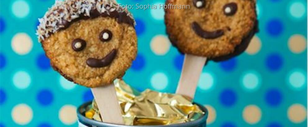 Smiley-Kekse auf Holzstäbchen in eine Dose gesteckt vor blauer Pünktchentapete