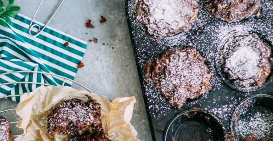 Schokoladige Zucchini-Muffins auf einem Gitter und in der Backform, von oben fotografiert.