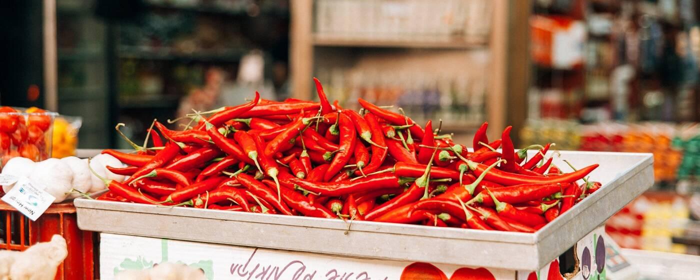 Eine Kiste voller Chili-Schoten auf einem Wochenmarkt, davor Ingwer
