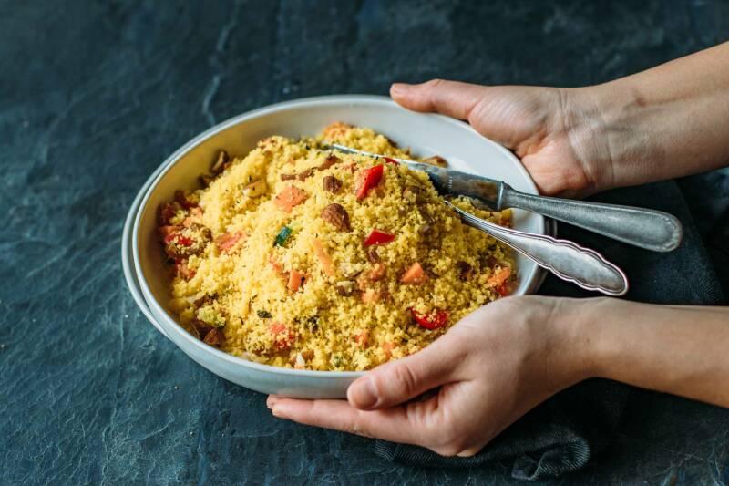 Helle, flache Schale gefüllt mit Couscous Salat, darin liegen noch Messer und Gabel. Dunkelgrauer Hintergrund, von oben fotografiert.