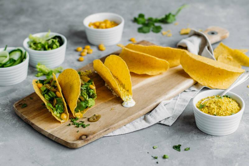 Couscous Tacos auf Schneidebrett mit Guacamole vor hellem Hintergrund.