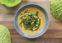 Wirsing-Erdnuss-Suppe in grauer Schale auf Holzbrett mit Wirsingblättern dekoriert