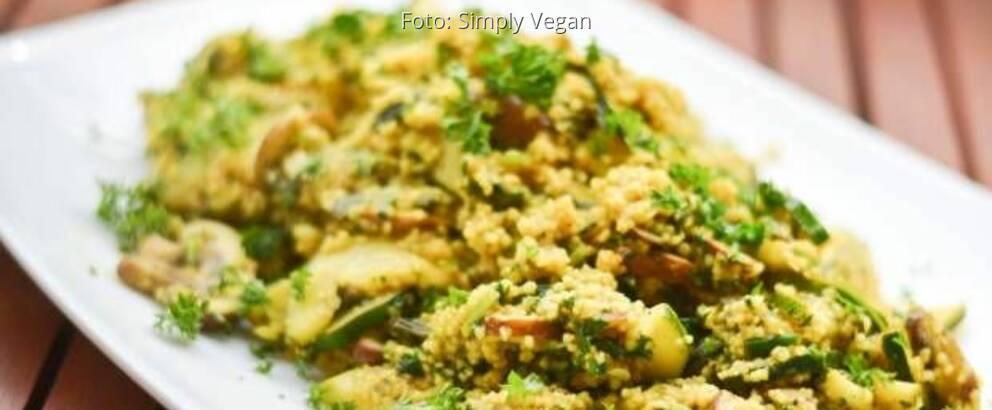 Couscous auf weißem Teller mit Zucchini, Champignons und Curry