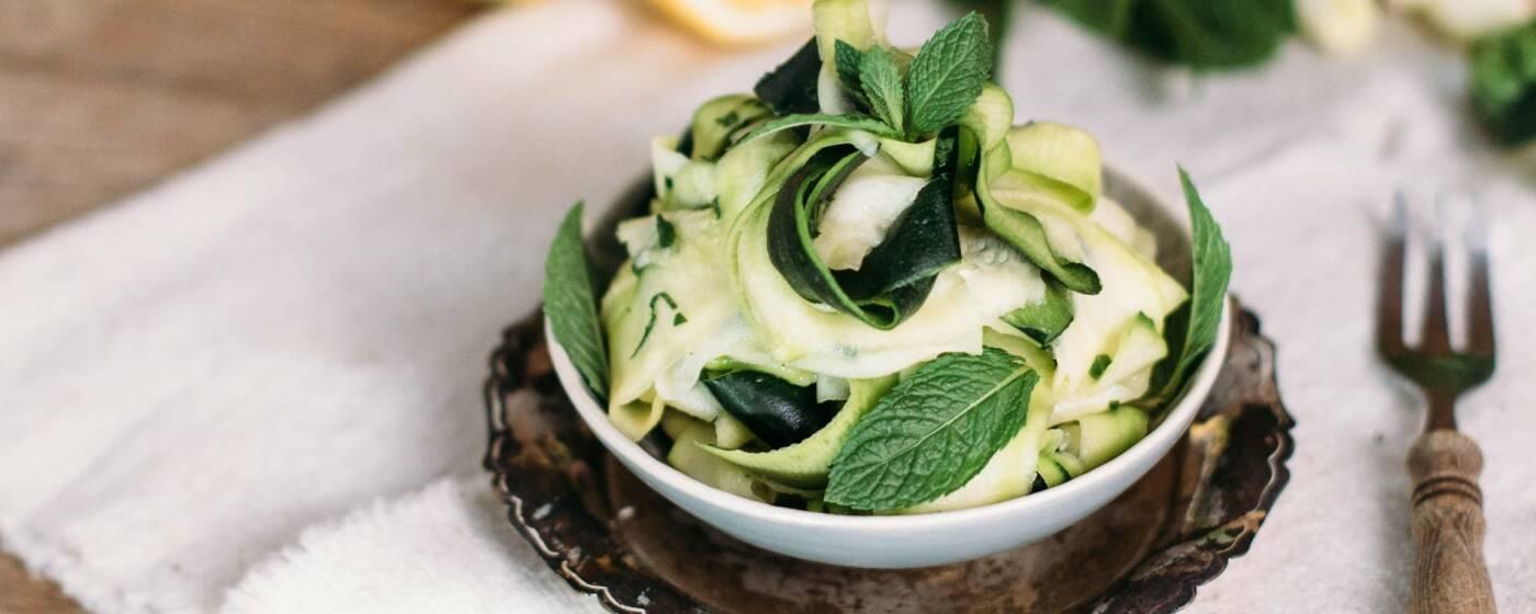 Roher Zucchini-Minz-Salat in einer Schüssel auf einer weißen Tischdecke, daneben eine Gabel mit Holzgriff.