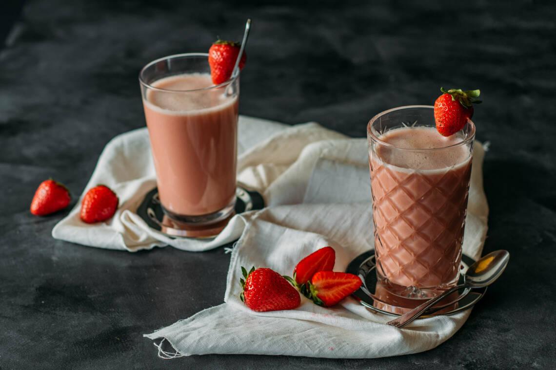 Erdbeer Smoothie in Gläsern vor dunklem Hintergrund.