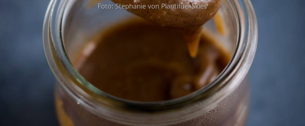 Glas mit selbstgemachter Erdnuss-Karamell-Sauce auf dunkler Platte