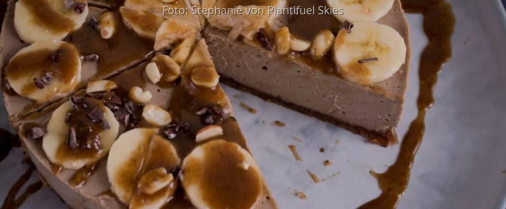 Torte aus Erdnussbutter auf großer heller Platte, dekoriert mit Bananenscheiben, Pinienkernen und Karamell