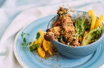 Masala-Spieße im Gomasiomantel in einer Schüssel, daneben Salat und Paprika. Blaues Geschirr, von oben fotografiert.