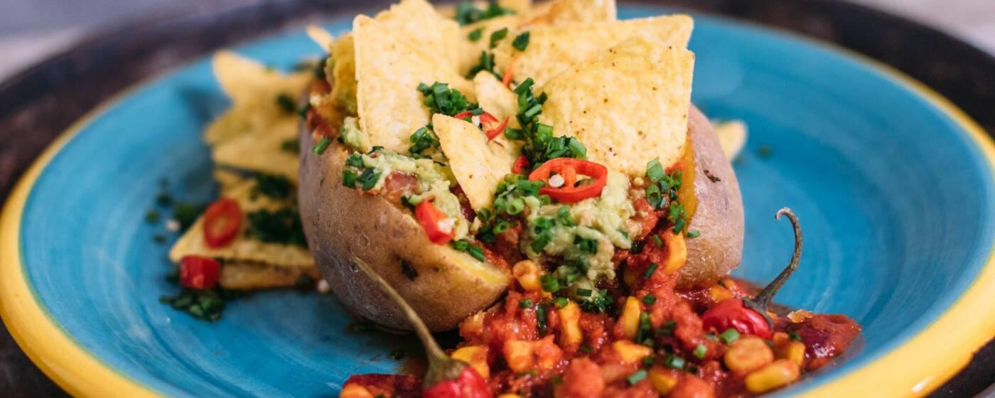 Mexican Potato auf einem blauen Teller: Kartoffel gefüllt mit Chili und Tortillachips.