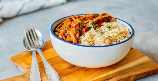 Weiße Schüssel auf einem Holzbrett gefüllt mit Reis und Tomaten-Bohnen-Gemüse. Daneben Besteck.