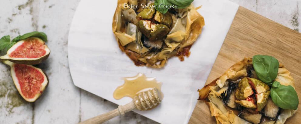 Zwei Asche Käse Tarteletts auf einem Brett mit Honig und Feigen