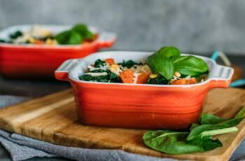 Flexitarischer Wochenplan mit fünf Gerichten: Gnocchi-Spinat-Auflauf in einer Form, auf einem Holzbrett. Basilikum zur Deko.