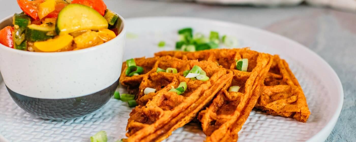 Süßkartoffel-Waffelecken auf einem flachen, weißen Teller, daneben eine Schüssel mit buntem Ratatouille-Gemüse.