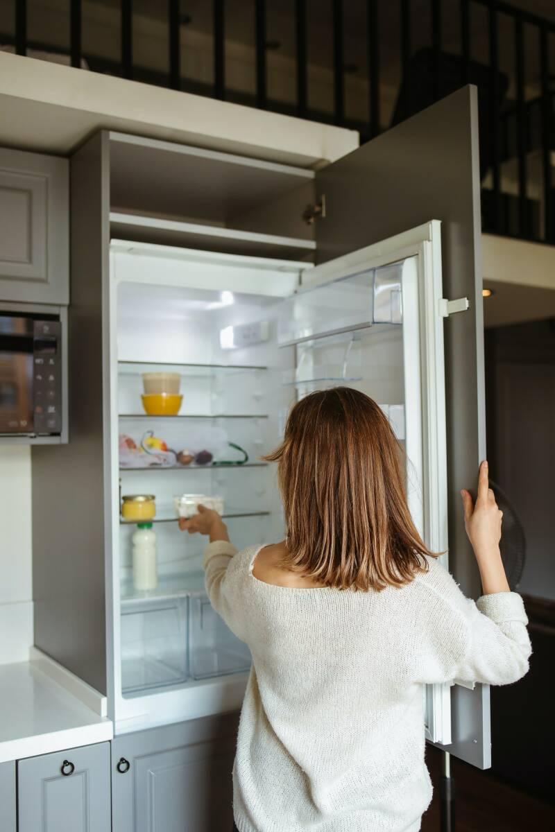 Frau vor Kühlschrank