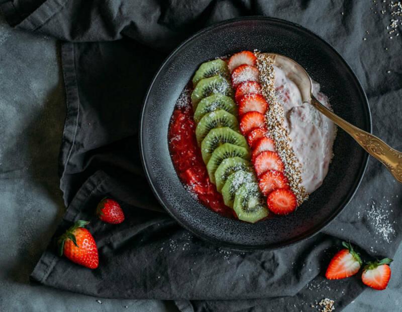 Frühstücksbowl mit Erdbeeren und Rhababer in Schüssel vor dunklem Hintergrund.