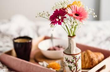 Frühstückstablett auf einem Bette, darauf Blumen, Kaffee, ein Croissant