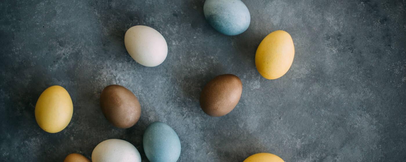 Gelb, blau und rot gefärbte Eier auf Marmorplatte