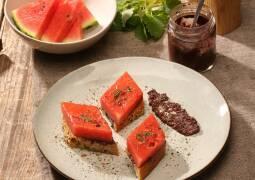 Teller mit gebratener Wassermelone, Olivnepaste auf Holztisch