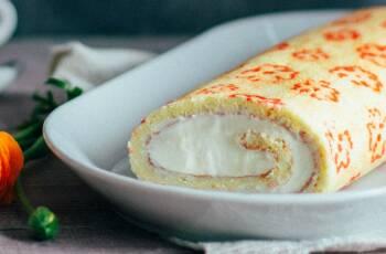 Biskuitrolle mit Zitronencreme auf einer weißen Platte, von vorne fotografiert.