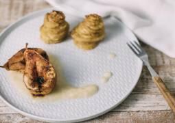 Holztisch mit weißem Teller, Gabel, Türmchen aus Kartoffelgratin und geschmorten Birnenhälften