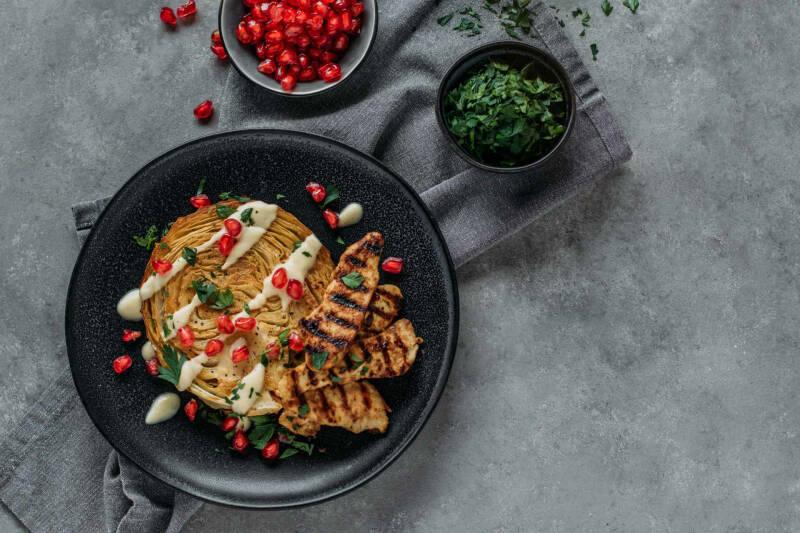 Geschmorter Weißkohl mit Putenstreifen auf einem schwarzen Teller mit Granatapfelkernen verziert.