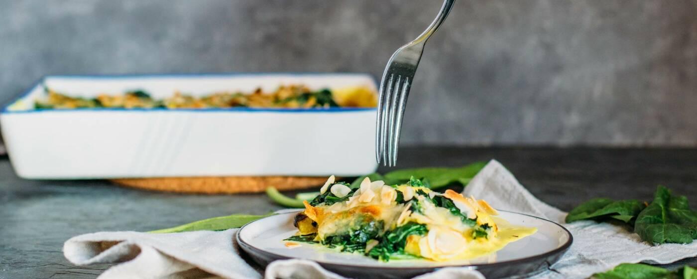 Leckerer Auflauf mit Gnocchi, Spinat und Curry-Note, überbacken mit einer Kruste aus Mandelblättchen und Mozzarella.