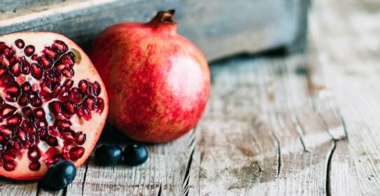 Halbierter Granatapfel auf Holz von seitlich oben