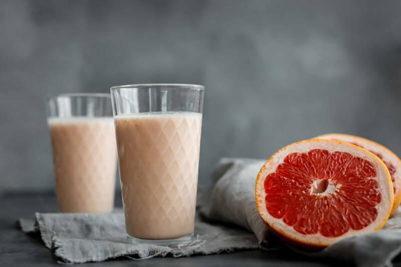 Grapefruit Smoothie in Gläsern neben Grapefruit vor dunklem Hintergrund.