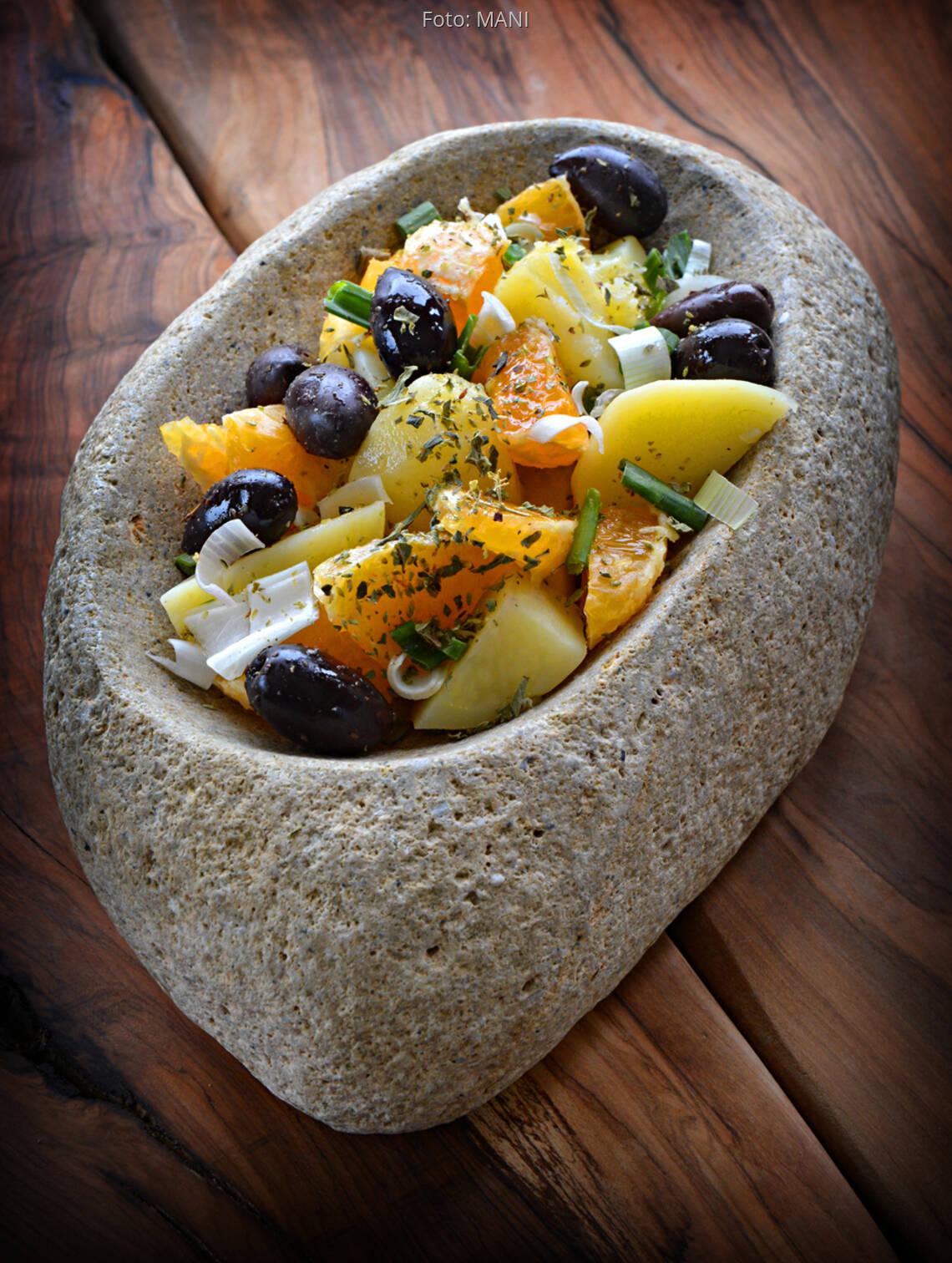 Steinschale mit Salat aus Kartoffeln, Oliven, Zwiebeln, Orange, Kapern