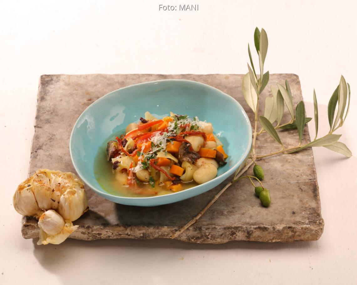 Bohnen-Eintopf in blauer Schale auf Holzbrett mit gebackenem Knoblauch und Olivenzweig