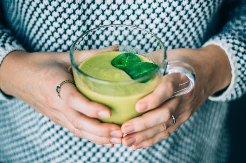 Frau schenkt grünen Smoothie aus einem Krug in ein Glas