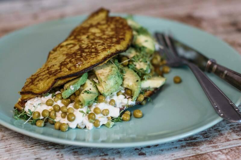 Grünes Frühstücksomelett auf Teller mit Besteck vor dunklem Hintergrund.