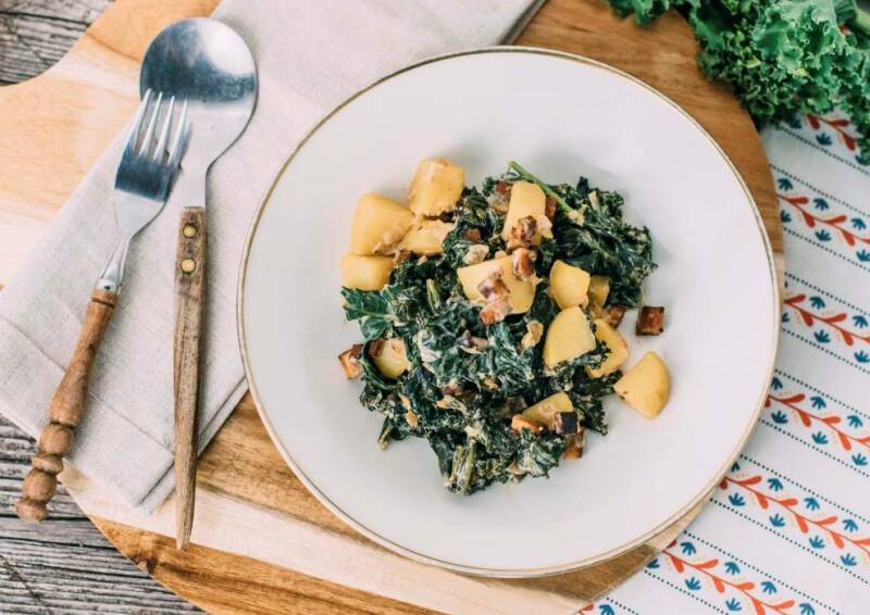 Grünkohl mit Kartoffeln und Räuchertofu auf einem Teller, daneben  Grünkohlblätter und Besteck, von oben fotografiert.