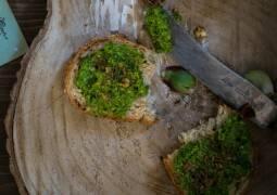 Holzscheibe mit zwei Brotscheiben mit Grünkohlpesto und Messer