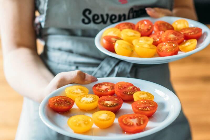 Schritt 4: Fertig halbierte Kirschtomaten auf einem weißen Teller, von vorne fotografiert.